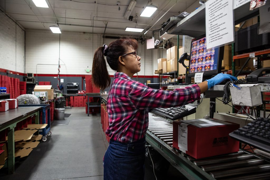 Copyrighted 2018 Ken Cooper | A woman in a plaid shirt works on a computer in the factory at Helwig Carbon